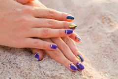 Women's hands with a nice manicure on the sand Stock Images