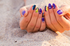 Women's hands with a nice manicure on the sand Royalty Free Stock Photography