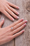 Women's hands on old vintage wooden background. Royalty Free Stock Image