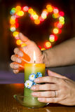 Women's hands over a burning candle on the background Bokeh Royalty Free Stock Photos