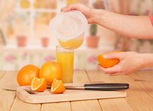 In women`s hands is part of orange and juicer, glass of orange j. In the women`s hands is part of the orange and the juicer with the juice, a glass of orange Stock Images