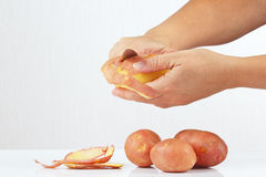 Women's hands peeling potatoes with a knife Stock Photos