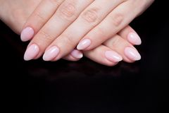 Women`s hands with perfect Nude manicure. Nail Polish is a natural pale pink shade. Black background. Close-up stock photo