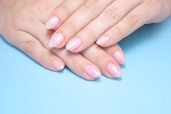 Women`s hands with perfect Nude manicure. Nail Polish is a natural pale pink shade. Blue background. Women`s hands with perfect Nude manicure. Nail Polish is a royalty free stock photos
