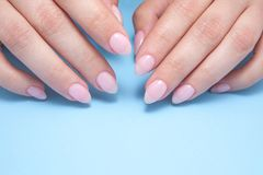 Women`s hands with perfect Nude manicure. Nail Polish is a natural pale pink shade. Blue background. Women`s hands with perfect Nude manicure. Nail Polish is a stock photos
