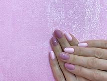 Women`s hands with perfect Nude manicure. Nail Polish is a natural pale pink shade. Close - up on pink background. Women`s hands with perfect Nude manicure. Nail royalty free stock images