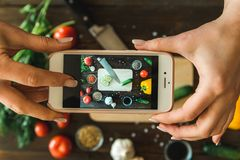 Women`s hands with a phone take pictures of vegetables. Horizontal frame Royalty Free Stock Photography