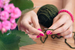 Women's hands with pink manicure knit metal spokes. Nearby is a pink flower in a pot. Knitting closeup Stock Images