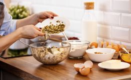 Women`s hands prepare dough with nuts and seeds for cookies Royalty Free Stock Photos