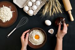 Women`s hands are preparing home-made raw noodles, Rustic, Selective Focus, Atmospheric dark tone. Food flat lay on kitchen table background. Working with Royalty Free Stock Images