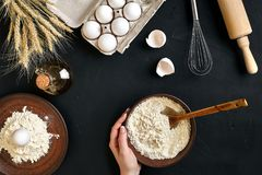 Women`s hands are preparing home-made raw noodles, Rustic, Selective Focus, Atmospheric dark tone. Food flat lay on kitchen table background. Working with Royalty Free Stock Photography