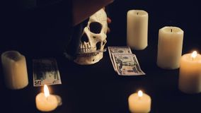 Skull with US Dollar bills in his mouth. Women`s hands pull banknotes out of the mouth of the skull. Candles are burning around the circle. Black background stock video footage