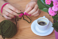 Women's hands with purple manicure are knitted metal spokes of a. Wooden table. On the table is a cup of coffee, flower pot and a green ball of wool yarn Stock Image