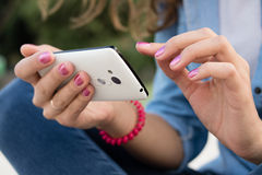 Women's hands with red manicure holding a modern mobile phone. With a touch screen. Young woman in denim clothes sitting on a beach and enjoying the wireless Royalty Free Stock Photography