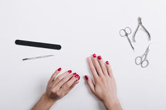 Women's hands with a red manicure scissors and nail file on a wh Royalty Free Stock Images