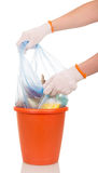 Women's hands are removed from bucket bag with waste. Women's hands are removed from the plastic bucket bag with household waste  on white background Stock Image