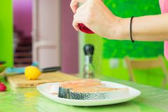 Women`s hands sprinkle from a handmade mills spices raw steak from salmon. Women`s hands sprinkle from the hand mill with spices two raw steak from salmon lying Royalty Free Stock Photos
