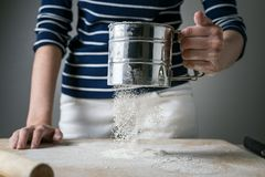 Women`s hands sprinkle a wooden Board with white flour for cooking. Dynamically frozen flour in flight.  stock photography