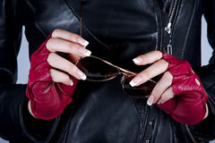 Women's hands with the sunglasses. Women's hands with a manicure with sunglasses in stylish gloves Stock Photography