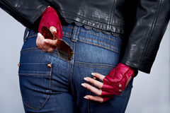 Women's hands with the sunglasses. In stylish gloves back on the background of jeans Royalty Free Stock Photos