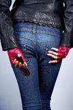 Women's hands with the sunglasses. In stylish gloves back on the background of jeans Stock Photo