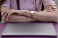 Women`s hands are on the table in front of a closed laptop royalty free stock image
