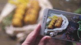 Women`s hands takes the phone Meat, steak, corn spices. The camera focuses first on the phone and then on the corn on the table.  stock video