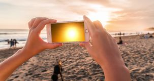 Women`s hands takes a sunset on a smartphone in the evening on the beach in cinemagraph style with timelapse stock video