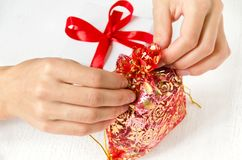 Women`s hands tie a small bag with gifts, next to a gift box on the table. White background Stock Photo