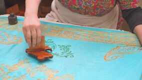 Women's hands to put drawings on women's silk shawls.