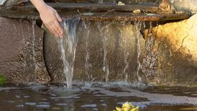 Women`s hands touch transparent water flowing down the stones, slow motion. Women`s hands touch transparent water flowing down the stones into a small pond, slow stock video footage