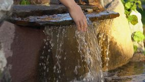 Women`s hands touch the water running down the rocks in an artificial pond. Women`s hands touch transparent water flowing over the stones into a small stock video footage