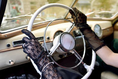 Women's hands in transparent gloves on the steering wheel of ret Royalty Free Stock Photos