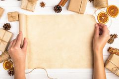 Women`s hands are turning the craft paper roll. Against the background of dried orange, cinnamon, pine cones, anise on a white ta. Women`s hands are turning the royalty free stock image