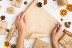 Women`s hands are turning the craft paper roll. Against the background of dried orange, cinnamon, pine cones, anise on a white ta. Women`s hands are turning the royalty free stock images
