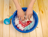 Women's hands wash clothes in blue pelvis. Close up Stock Photos