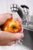 Women's hands washing an apple, closeup Stock Image
