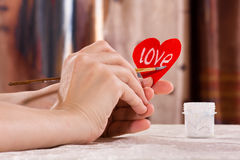 Women's hands writing on the paper heart for Valentine's day Royalty Free Stock Photo