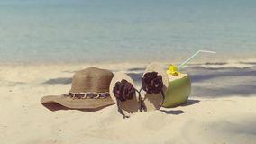 Women's hat, flip-flops and coconut , lonely lying on the sand near the sea. stock video footage