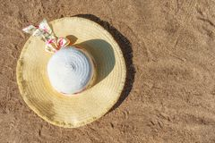 Women`s hat on the sandy beach. Top view. Background with copy space. Women`s hat on the sandy beach. Top view. Background with copy space Stock Photo