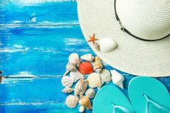 Women`s Hat Slippers Various Kinds of Spiral Flat Sea Shells Red Star Fish on Aged Plank Wood Blue Background. Summer Vacation. Travel Wanderlust Concept stock photography