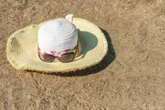 Women`s hat and sunglasses on the sandy beach.  Royalty Free Stock Images