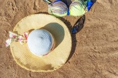 Women`s hat, sunglasses and swimsuit on the sandy beach. Top view. Background with copy space. Women`s hat, sunglasses and swimsuit on the sandy beach. Top view Royalty Free Stock Photography