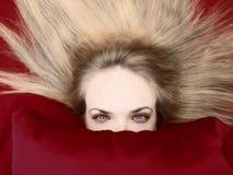 Women's head behind pillow Stock Image