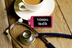 Women& x27;s health. Medical concept. Stethoscope ,a cup of coffee and wooden board with words WOMEN& x27;S HEALTH on wooden table stock image