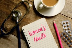Women& x27;s health. Medical concept. Top view of a cup of coffee,pink pencil,stethoscope,medicine and book written with WOMEN& x27;S HEALTH on wooden background stock photography