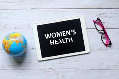 Women& x27;s health. Top view of globe of world map, pink sunglasses and tablet computer written & x27;WOMEN& x27;S HEALTH& x27; on white wooden background stock photo