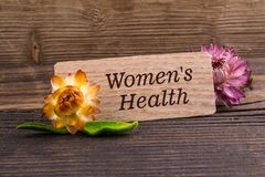 Women`s health. Text on wooden card with dried flower on wood royalty free stock photo