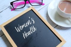 Women`s health written on a blackboard. Sunglasses,a cup of coffee and blackboard written with `WOMEN`S HEALTH` on white wooden background. Healthcare and Stock Image