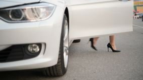 Women`s heels come out of an expensive car and closes the doors of a car. Woman legs in high heels at the car in the. Footage was made with fullframe Nikon D850 stock video